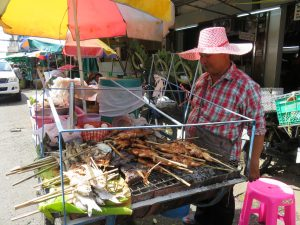Meat sizzling on a Bangkok food cart